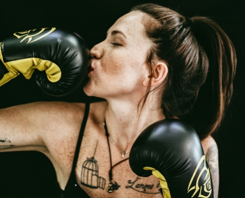 woman kissing a boxing glove